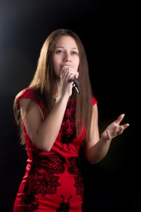 Young female singer in red dress